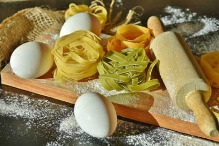 Fresh homemade tagliatelle with eggs, rolling pin, and flour spread on cutting board